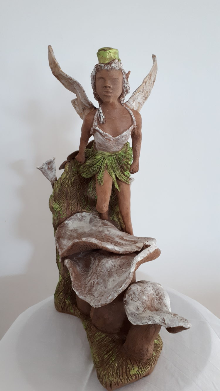L'elfe ets une sculpture en grés, ici de face, patinée de vert et de blanc