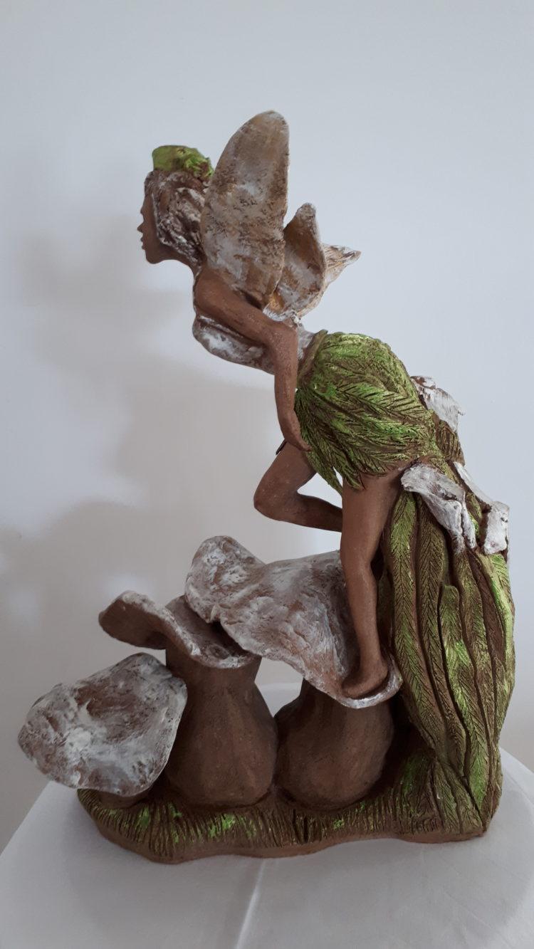 De côté, la sculpture de l'elfe semble préparer son envol. En grés, patinée de vert et blanc