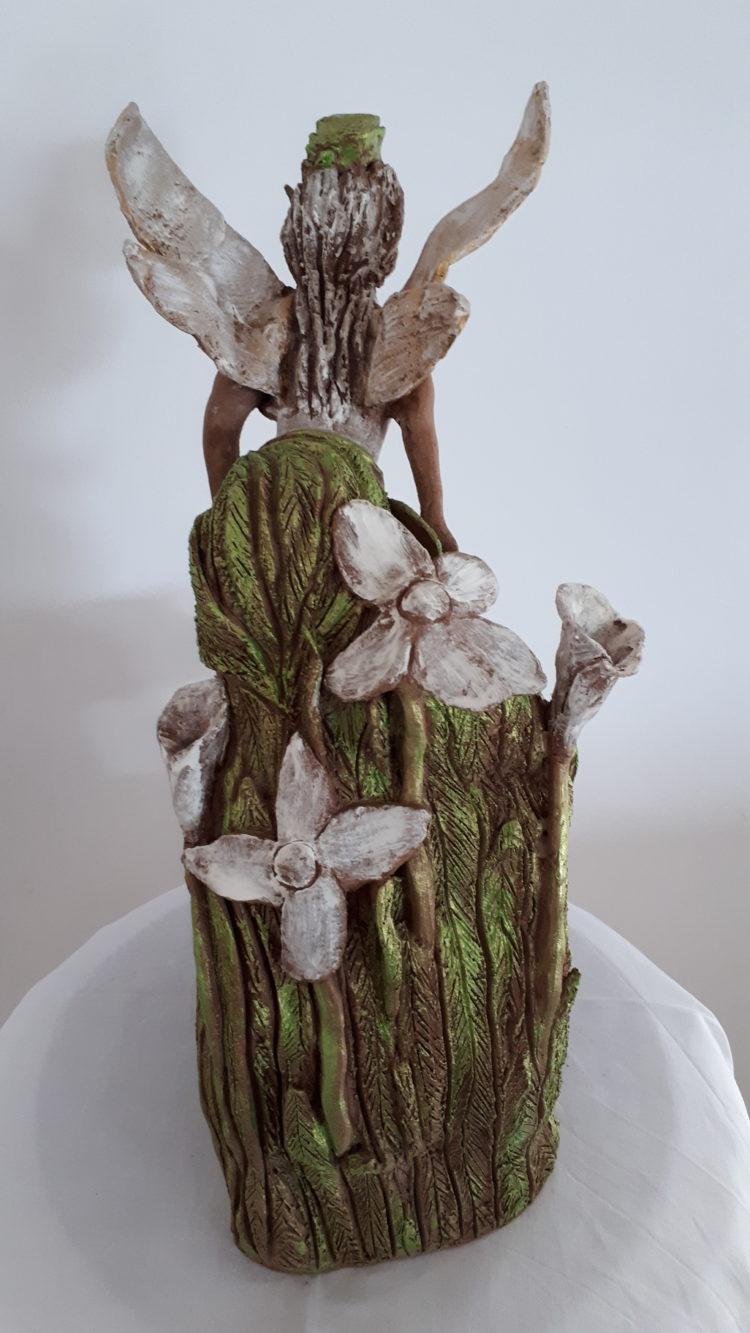De dos, la sculpture de l'elfe, laisse découvrir un socle naturel et fleuri. Création en grés, patinée en vert et blanc