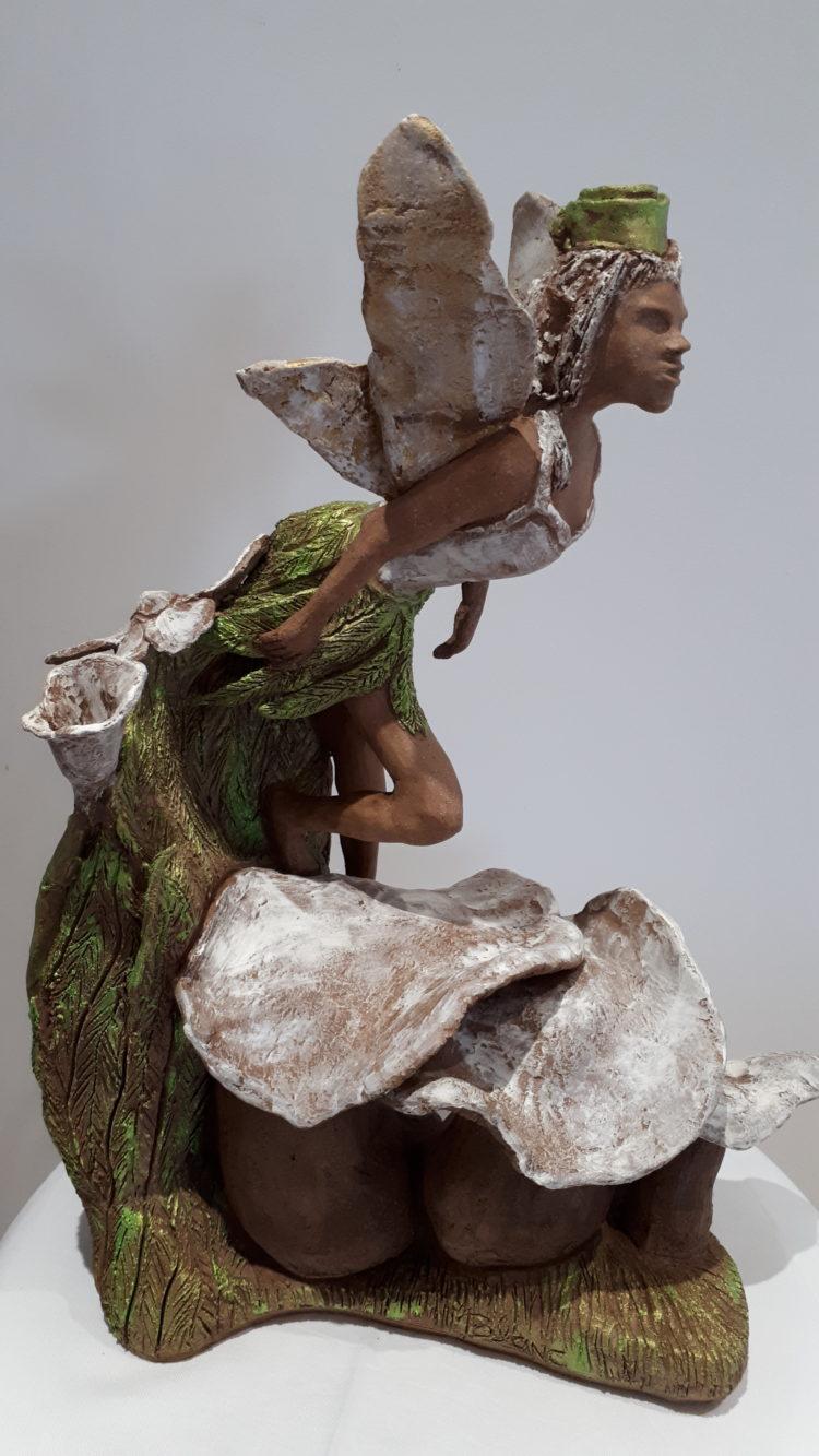 Sur son socle végétal, l'elfe en grés, prépare son envol. Les patines verte et blanche habillent la sculpture