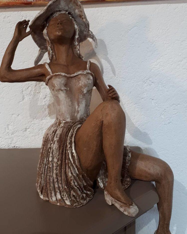La dame au chapeau, de face, est une sculpture en grés patinée de blanc