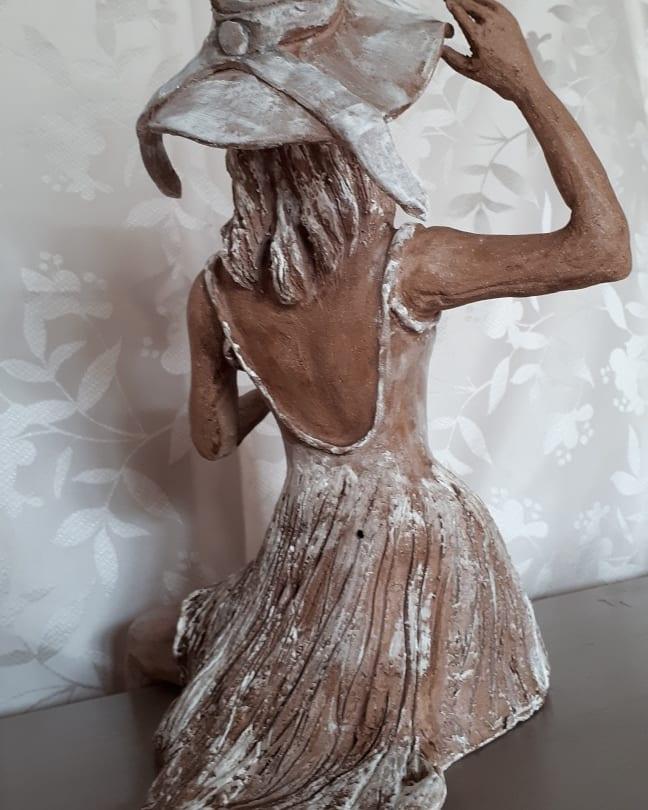 Totalement de dos. La dame au chapeau est une sculpture en grés. Certaines zones sont patinées de blanc
